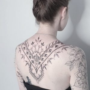 mandala fine line tattoo on the back of a woman